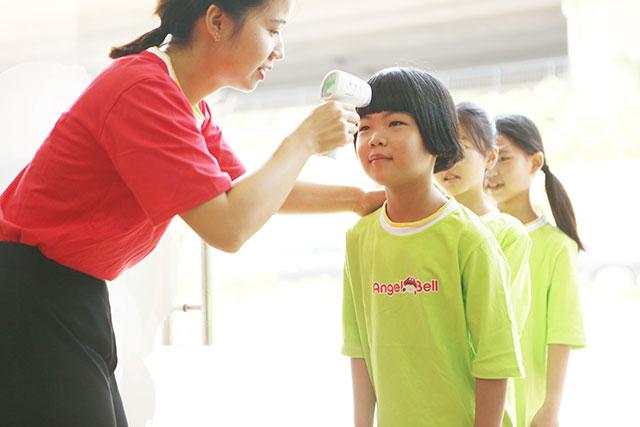托管老师为孩子测量体温